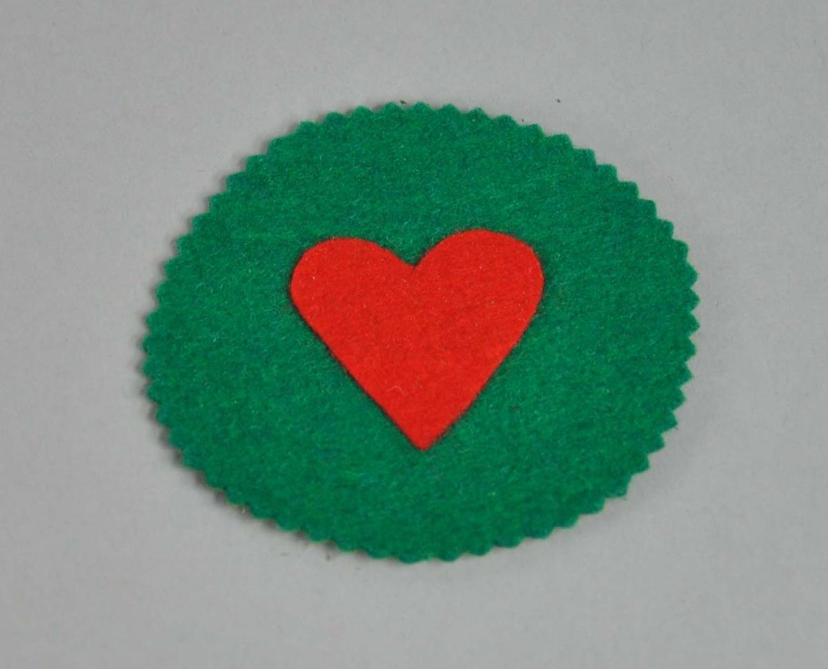 Rund brikke av grønt stoff, med bølgete kant. På midten er symbolet for hjerterkortet.
