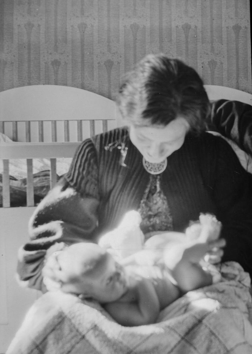 Kvinne med et lite barn, dobbeltseng i bakgrunnen, på Birkely