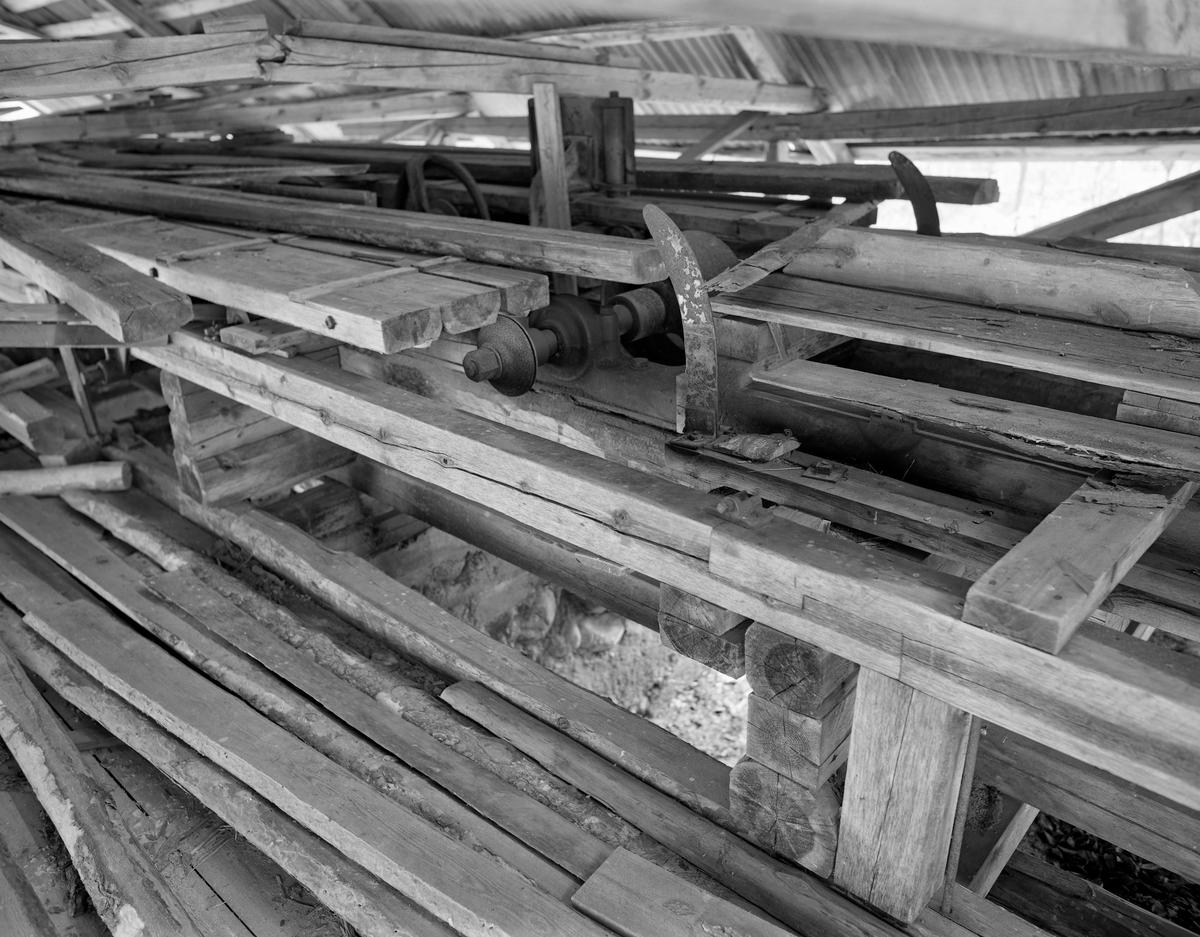 Interiør fra saghuset på Mastveltsaga i Åsnes i Solør.  Fotografiet er sommeren 1975, da lokomobilen og saginnredningen fra dette anlegget ble demontert og flyttet til et nytt saghus på Norsk Skogmuseum (fra 2003 Norsk Skogbruksmuseum) i Elverum.  Dette fotografiet er tatt mot sagbenken og de to spindlene, som på dette tidspunktet manglet sagblad.  Interiøret framsto på opptakstidspunktet som noe rotete.  Mer informasjon om Mastveltsaga og om lokomobilsager generelt finnes under fanen «Opplysninger».