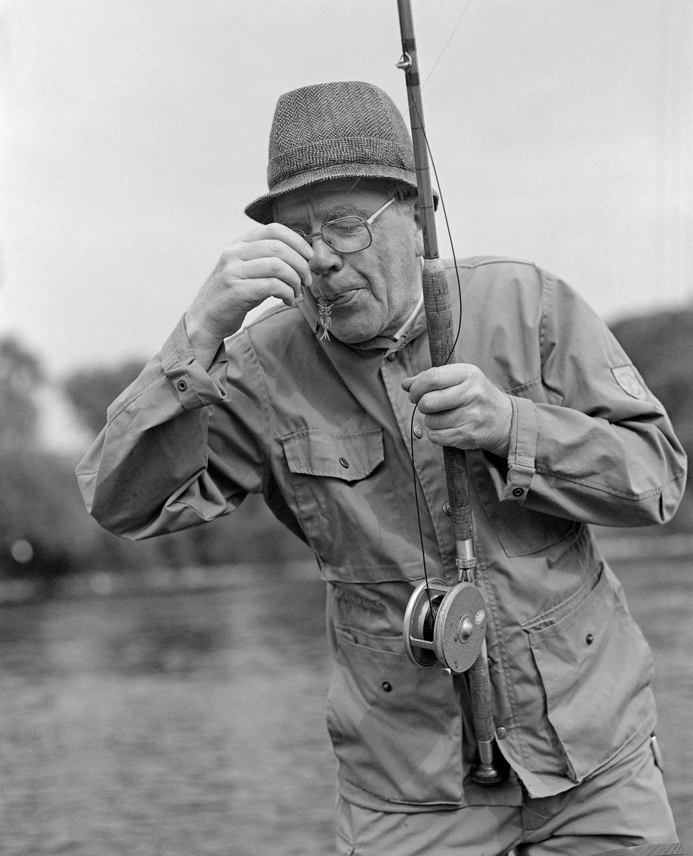 Asbjørn Hørgård (1910-2001), fotografert under fiske i Nidelva sør for Trondheim by.  Fiskeren hadde sportsjakke på overkroppen, hatt på hodet og vadere på beina.  Fluestanga og snella han brukte, var trolig fra bedriften han sjøl hadde bygd opp, Asbjørn Hørgård AS i Trondheim.  Det var også agnet som han spyttet på da dette fotografiet ble tatt, en døgnfluenymfeetterlikning av gummi som var festet til en fiskekrok.  Dette produktet ble levert i ulike størrelser, farger og tyngder, og det ble markedsført under navnet «May Fly Nymph», både for ferskvannsfiske og havfiske.  Fotografiet er sannsynligvis tatt i nærheten av bedriften, ved Nidelva, på et tidspunkt da gründeren Asbjørn Hørgård var midt i 70-åra og hadde overlatt ledelsen av virksomheten til neste generasjon.  Mer informasjon om Asbjørn Hørgård og hans produksjon av splitcanestenger og annet fiskeutstyr finnes under fanen «Opplysninger».