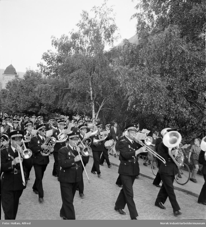 Musikkorps marsjerer i Rjukan en mai-dag.