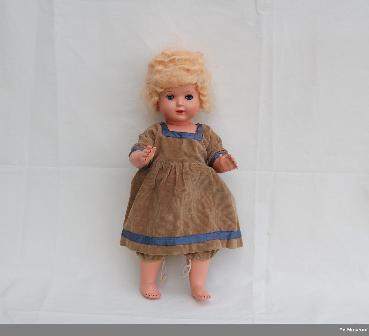 Sovedokke med kjole, bukse og pålimt parykk. Dokka (c) har neglelakk på tær og fingre, leppestift, og pålimte augevipper. Det er strikk i hofteledda og skulderledda. Kjolen (a) har høgt liv, korte ermer og firkanta hals. Det er påsydd band rundt halsen, armane og nederst på kjolen. Det er tre trykknappar i ryggen. Sikkerhetsnål der ein knapp kan ha losna. Buksa (b) har snor og løpegang i livet og og beina.