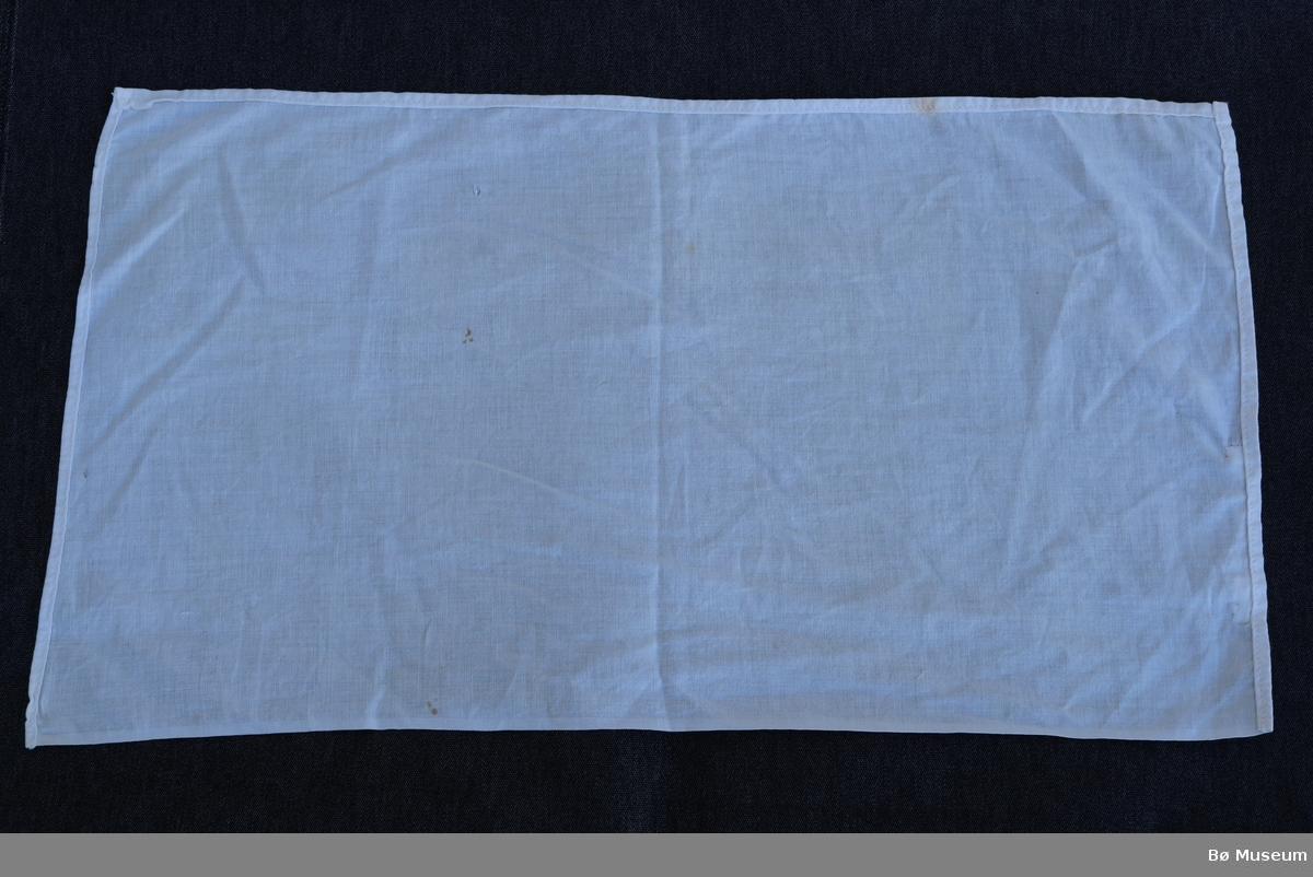 Dokkeseng i tre (a), med madrass (b), skumgummi (c), pute (d), dyne (e), laken (f) og teppe/kladd (g).   Senga (a) har gavl. Det er sprinkelverk i fotenden. Det er treplankar i botn. Det er feste til sprinklar i hovudenden, men manglar sprinklane. Målinga er slite av nokre stader. Nokon sprekkar der det er sett inn spiker. Opprinneleg måla i grønt, så måla over med blått, men den eine sida er ikkje måla andre gongen.   Madrassa (b) har stripete trekk og plass til fire knappar. To av knappane er borte. Det er sydd att eit hol på den eine sida. Nokre flekkar. Vattfyll.  Skumgummien (c) er firkanta og skore slik at han fyller ut senga saman med madrassa.   Puta (d) har laken som er festa med to trykknappar. Dyna (e) har ikkje laken. Lakenet (f) har fall i begge kortsidene og ei av langsidene.   Kladden (g) har mønster i stoffet og er noko slitt.