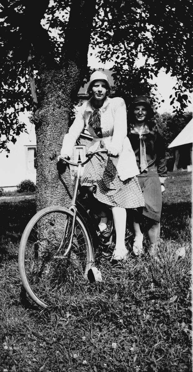 67620aea4565 Två yngre kvinnor på en cykel vid ett träd i trädgården. De är uppklädda med
