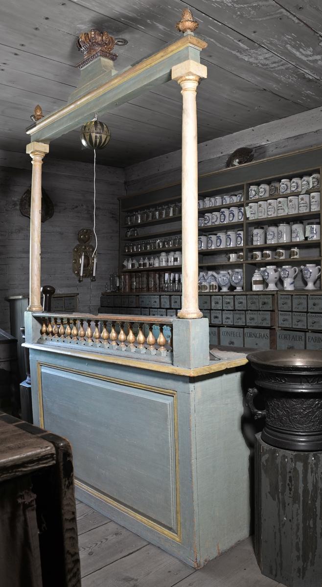 Receptur av trä målad i gråblått och guldfärg. Består av arbetsbänk och därunder lådinredning, bestående av två rader lådor med fackindelning och dragknoppar, sammanlagt 9 lådor (varav 2 lådor saknas). Under lådor ett hyllplan. På bordets front balustrad med guldfärgade balusterdockor samt två kolonner som bär upp en tvärbjälke med en kunglig krona och två kottar. På kolonnerna hjärtformade metallbeslag för upphängning.