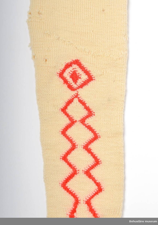"""Handstickade strumpor av vitt ullgarn, slätstickade med sicksack-mönster i aviga maskor med rött ullgarn längs fötterna och halvvägs upp på skaften, på både in och utsida. Överst har strumporna en kant mönstrad med aviga och räta maskor. Märkta UM 4:B:I och II. Enligt Knut Adrian Anderssons katalog I:5:4, D 2 A:1 i museets arkiv, är strumporna """"stickade ur minnet av en gammal kvinna på Inland i början av 1900 talet"""". I samma katalog står även att de vita strumporna skänkta 1910 av Bertha Kleberg är stickade av """"gummor på Inland"""". Små hål på många ställen. Flera lagningar bl a en lagad lång reva på ena skaftet. Strumporna diskuteras och är avbildade i Centergran (2010) s. 27-28.  Litteratur om Bertha Kleberg och om revitalisering av bygdedräkter: Arill, David, Bertha Kleberg och Bohusdräkten ur Bohusländska folkminnen Studier och uppteckningar red Arill, David, Uddevalla 1922. Centergran, Ulla, Folkdräktsrörelsen i Bohuslän och Göteborg, C-uppsats i etnologi, Göteborg 1973, Bygdedräkter bruk och brukare, Göteborg 1996.  Centergran, Ulla. Bohusdräkter. Tolkningar under ett sekel. Bohusläns museum och Bohusläns hembygdsförbund, nr. 71. Bohusläns museums förlag. Andra upplagan 2010.  Wistrand P G, Bohusländska folkdräkter ur Fataburen häfte 1 1908. STÖDTYG FASTTRÅCKLAT INUTI SKAFTEN PÅ BÅDA STRUMPORNA Omkatalogiserat 1997-03-20 VBT  Enligt uppgifter på diarienummer 184/69 KVINNLIGA DRÄKTPLAGG FRÅN BOHUSLÄN TILL UDDEVALLA MUSEUM: Strumporna 4a, 4b, 4c är stickade av gummor på """"Inland"""" i början av 1900-talet. ...  Ur handskrivna katalogen 1957-1958: Strumpor 3 par. a) Ett par  a) 1-2 L. c:a 62 cm; röda, ylle, stickade m. resår i skaftets översta del; malhål.  b) ett par b:1-2; L. c:a 67 cm, ylle, vita m. instickade röda kilar; malhål.  c) Ett par c: 1-2; L. c:a 55; vita, bomull, m. instickade  röda kilar, några rostfläckar.   Lappkatalog: 78"""