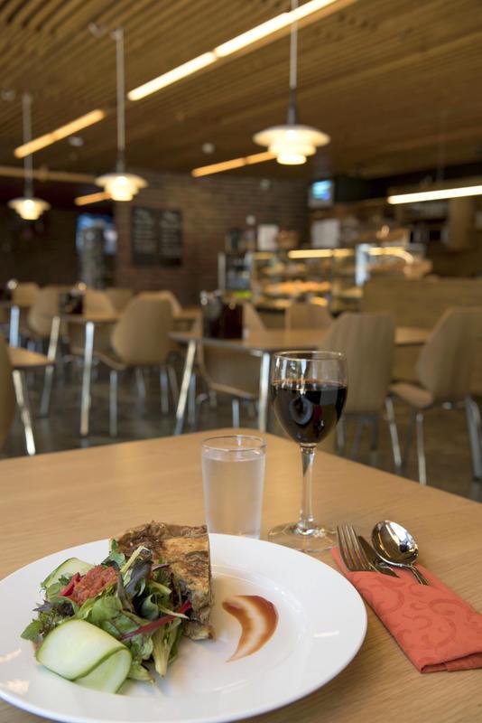 Tallerken med pai og glass med rødvin på bord. Kafeen i bakgrunnen