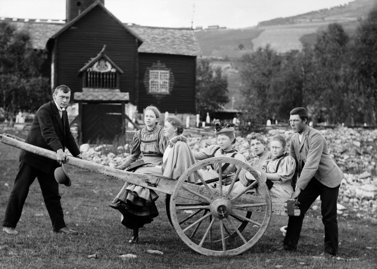 Fem unge jenter på ei kjerre utenfor Sødorp kirke med en ung mann foran og en bak. Sødorp kirke ble flyttet 1910
