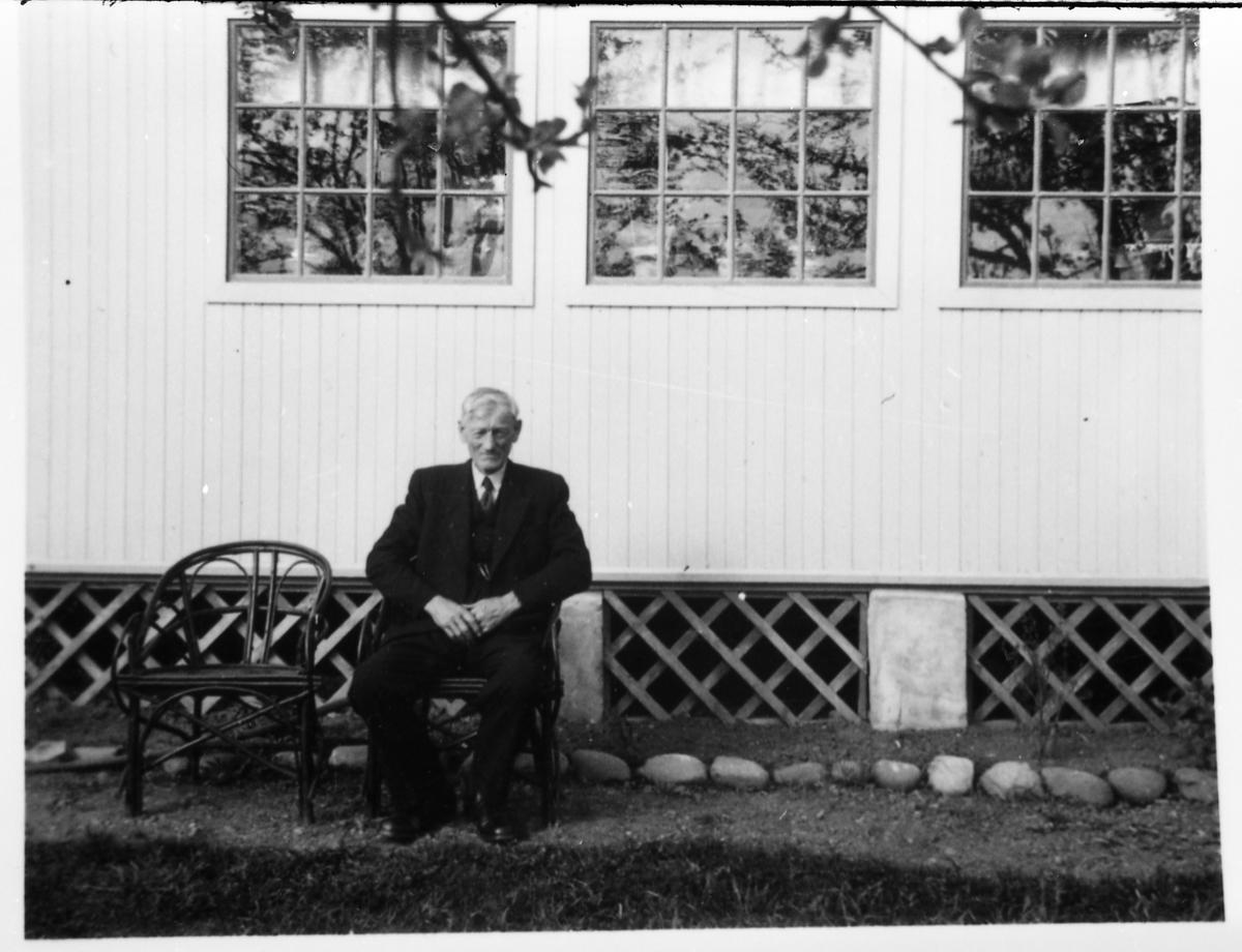 Avfotografert portrett av en uidentifisert mann som sitter foran en husvegg.