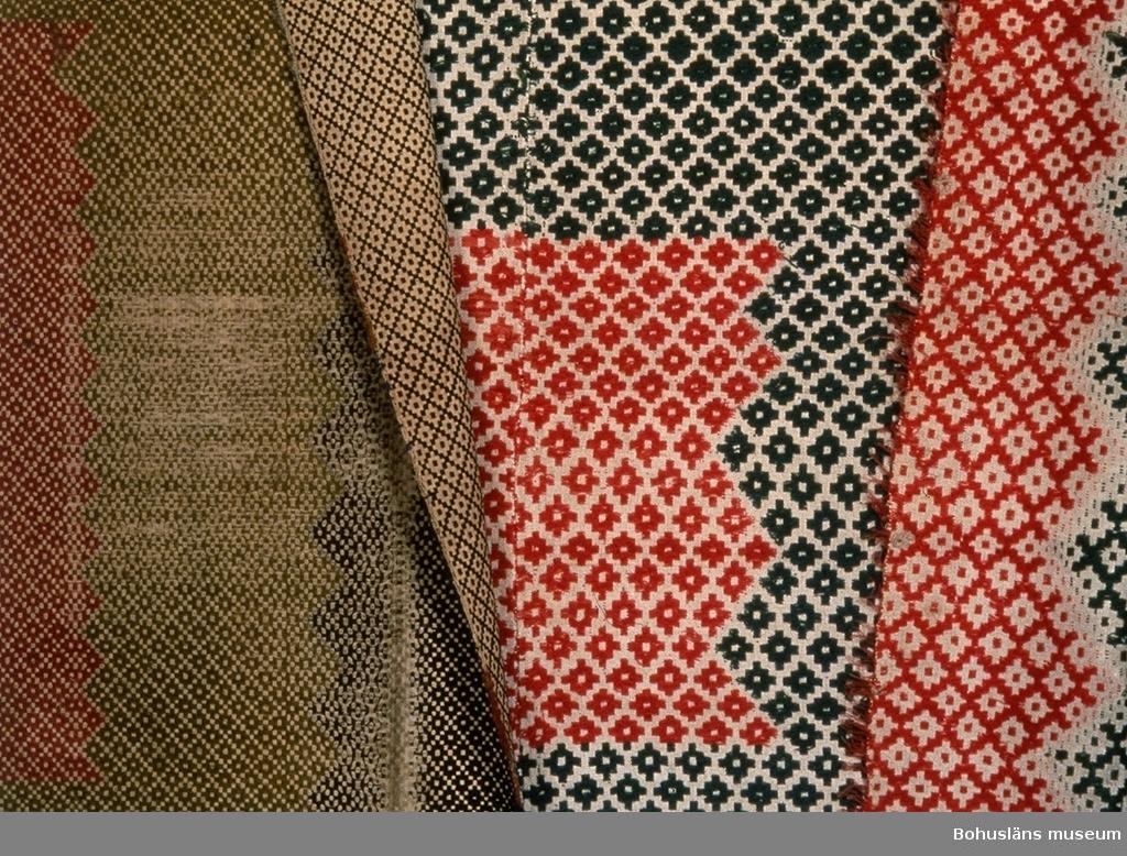 """412 Förvärvstillst VÄLBEVARAD (Täcket till höger på fotografi nr. 2) Täcke av två våder, ihopsytt med länsgående söm. Vävt i solvad upphämta med delvis inplockat mönster (flera olika trådar används över vävbredden och snärjs om varandra där de möts).  Bottenväv i tuskaft av beige lingarn. Mönsterinslag av tvåtrådigt ullgarn (kamgarn) och entrådigt ullgarn (det ljust gultonat röda), troligen syntetfärgat. Täcket har ett mittfält där solvning och trampning ger ett ytmönster med små romber och det inplockade mönstret består av en ljusröd  mitt ruta med taggiga kanter, runt den en bred ram (med taggig kant) i blåaktigt grönt, utanför den ytterligare en smalare ljusröd ram.  Över och under mittfältet finns bårder med rutor, kors och kantiga romber. Färgerna i bårderna är ljusrött, ljust gultonat rött (skärt), blågrönt och mörkt blått. Mönsterinslagen i bårderna är inskyttlade. Bården vid ena kortsidan är bredare än vid den andra. Rester av korta öglade fransar av mönsterinslaget finns längs långsidorna.  På fastnäst etikett står: """"Tillhör Gbgs o Bohusläns Hemslöjdsförening nr 2 Spegeltäcke opphämta fr Hammar ...(oläsligt) Harestad Inlands ... (oläsligt)"""".  Täcket har även en fastsydd etikett fråm Jubileumsutställningen i Göteborg 1923, märkt med ett rött kryss, utan skriven text. I en inventarieförteckning från Hemslöjdsföreningen på 1930-talet beskrivs nr 2 som """"Elvasolvstäcke från Hammar nederg. Harestad"""". Enligt tidigare kataloguppgift är täcket ursprungligen förvärvat från P.G.  Hammar, Harestad, Inland av Berta Kleberg. Solvad upphämta uppkallades efter hur många skaft som användes till  väven, dock är litteraturen oklar vad gäller om bottenskaftens antal  ska räknas in. Detta täcke har åtta olikvävande partier i mönstret,  därför kan det inte vara ett """"elvasolvstäcke"""". Dess utseende stämmer  inte heller överens med övriga täcken som kallas spegeltäcke. Mönsterinslaget i bården (och på ett ställe till) bitvis bortslitet. Smutsigt.  Litt; Berg, Kerstin, Selma Johanss"""