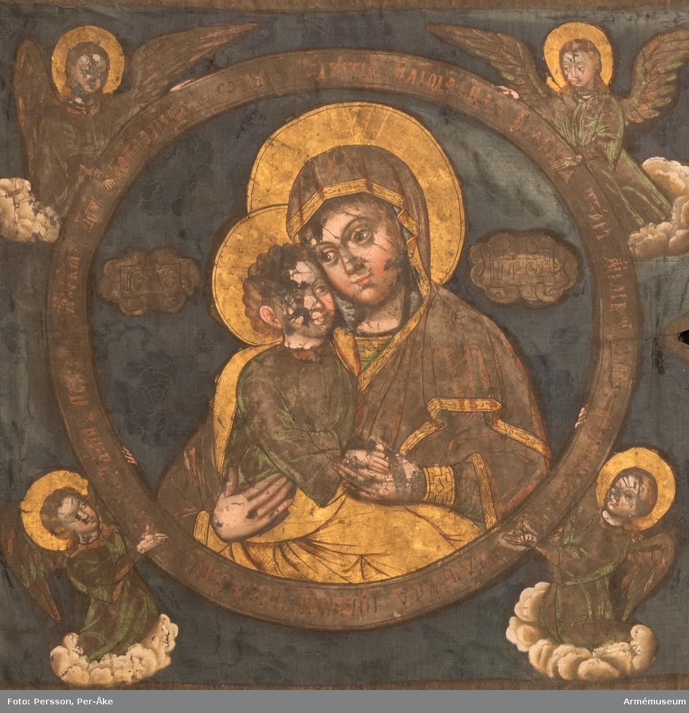 """Tvåtungad duk av blå kinesisk sidendamast. Strumpa av rött kläde. Motivet målat med guld- och silverfärg. Maria och Jesusbarnet återges i den komposition som kallas """"Ömhetens Gudsmoder"""". Den av änglar burna medaljongen pryds av rysk inskrift som i översättning lyder: """"Över dig, Fader, gläds var skapad varelse, änglarnas skara och människosläktet. Du ger ljus åt de rättrognas kyrka. Vi, dina barn, lovsjunga dig, milde Fader."""" Motivet är lika på båda sidor men av stilen att döma är de målade av olika konstnärer."""
