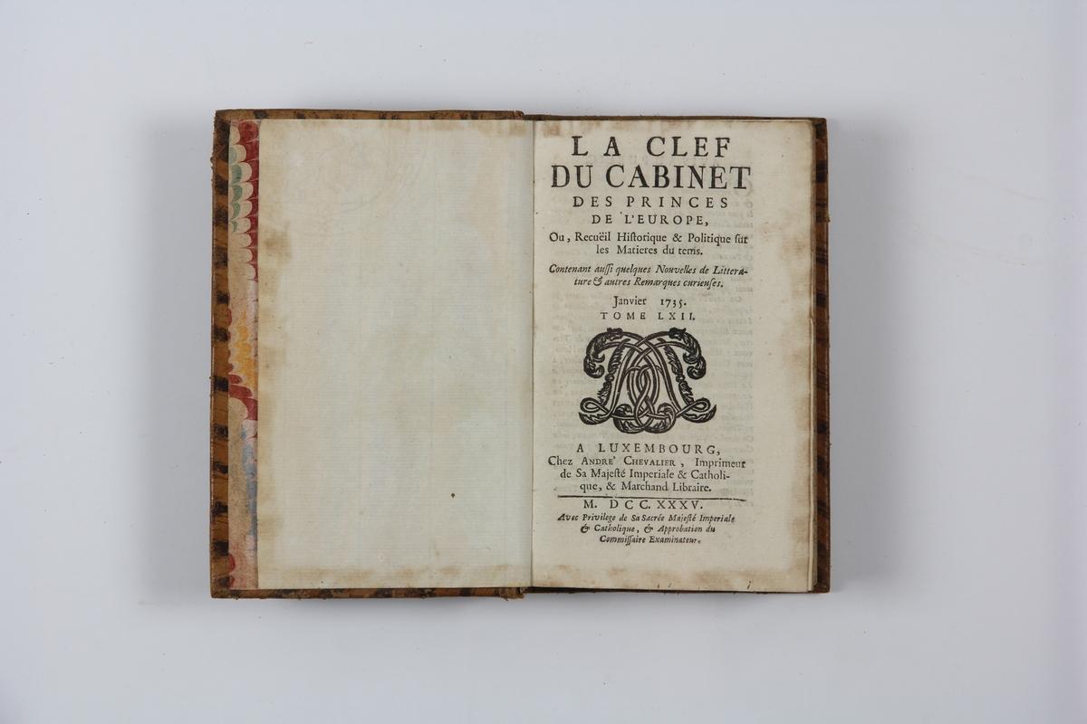 """Bok, helfranskt band """"La clef du cabinet des princes de l´Europe"""", del 62, tryckt i Luxemburg 1735. Skinnband med blindpressad och guldornerad rygg i fem upphöjda bind, titelfält med blindpressad titel,  fält med volymens nummer, fält med ägarens initialer samt påklistrad pappersetikett. Marmorerat papper på pärmarans insida.  Med rödstänkt snitt."""