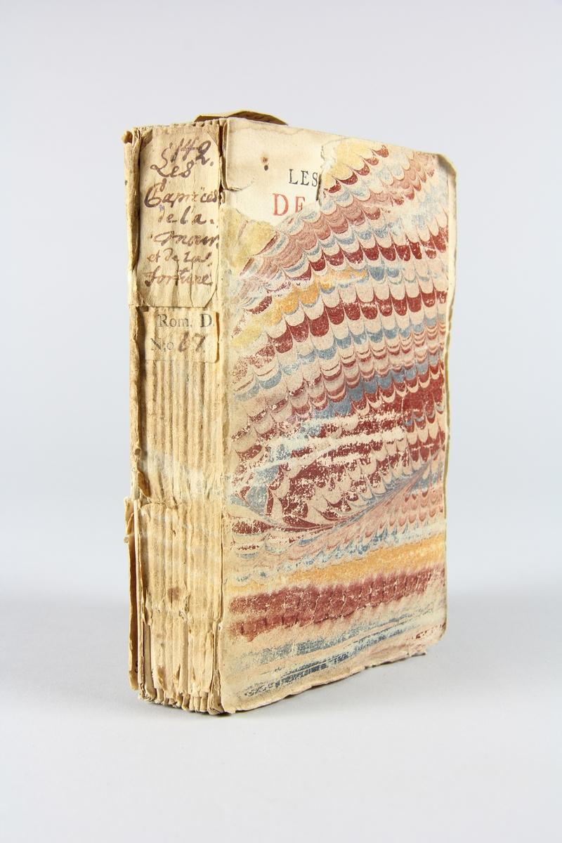 """Bok, häftad """"Les caprices de l´amour et de la fortune"""", tryckt 1737 i Haag. Pärm av marmorerat papper, oskuret snitt. På ryggen etikett med titel och samlingsnummer. Anteckning om inköp."""