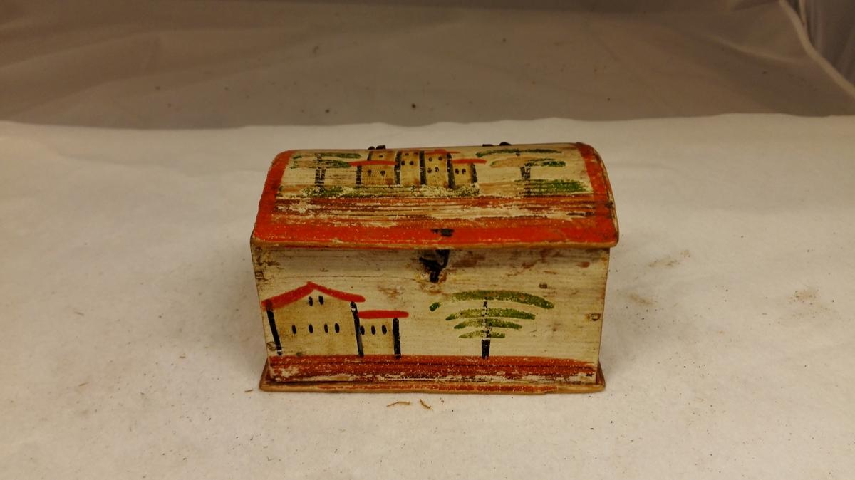 1 litet skrin.  Litet firkantet avlangt skrin med hvelvet laag, der har strenghængsler og strengkrok. Størrelsen 11,5 x 6,7 x 6,8 cm. Paa hvitmalet grund er i grønt, gult, rødt og sort malet trær og huser paa sider og laag. Gave fra Synneva L. Tømmerlid, Amble.