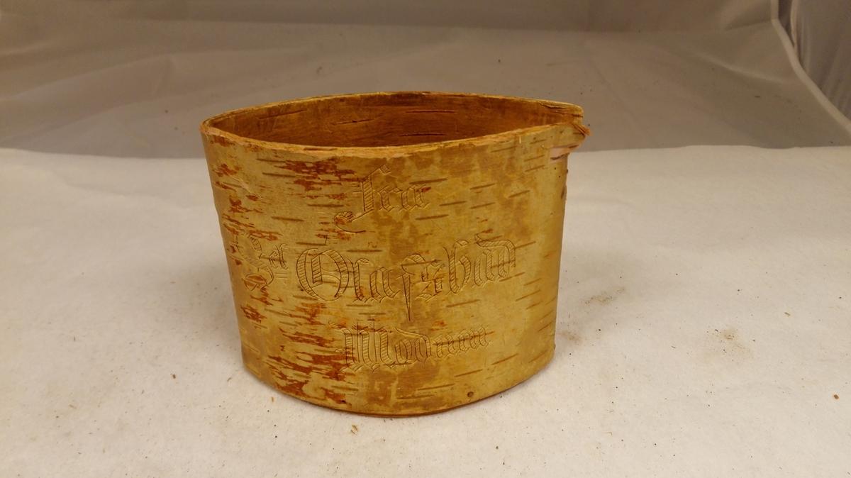 """Form: Elipseforma med spisse ender. 1 næveræske.  Liten æske av birkenæver med indsat bund og laag, hvori en skindreim hempe. Høide 10,2 cm, tverrsnittet eliptisk med spisse ender. Paa den ene side indskaaret """"Fra Sct Olafs bad, Modum."""" Kjøpt av giveren der i 1860 aarene. Gave fra fru Marie Heiberg, Amble."""