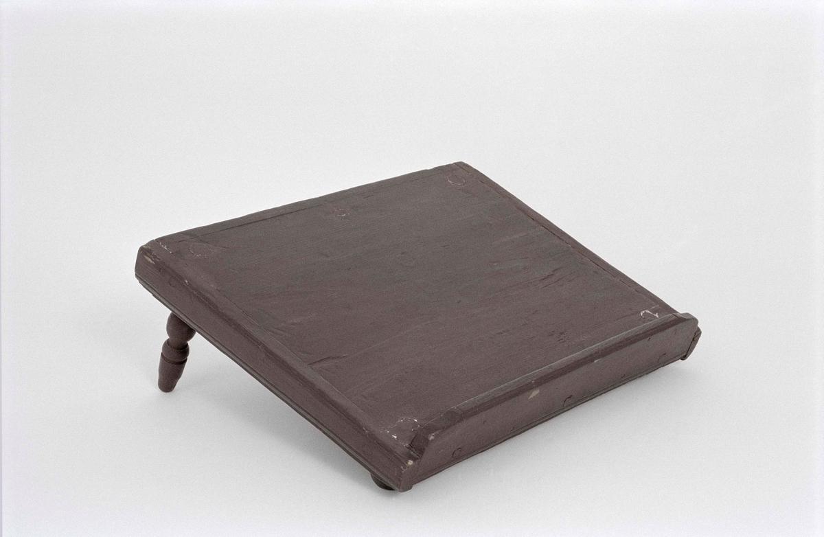 Bokpall av furu, målad brunröd. Med två längre och två kortare svarvade fötter som får pallen att luta. Pallens sidor profilerade, utmed främre långsidan en hög list.