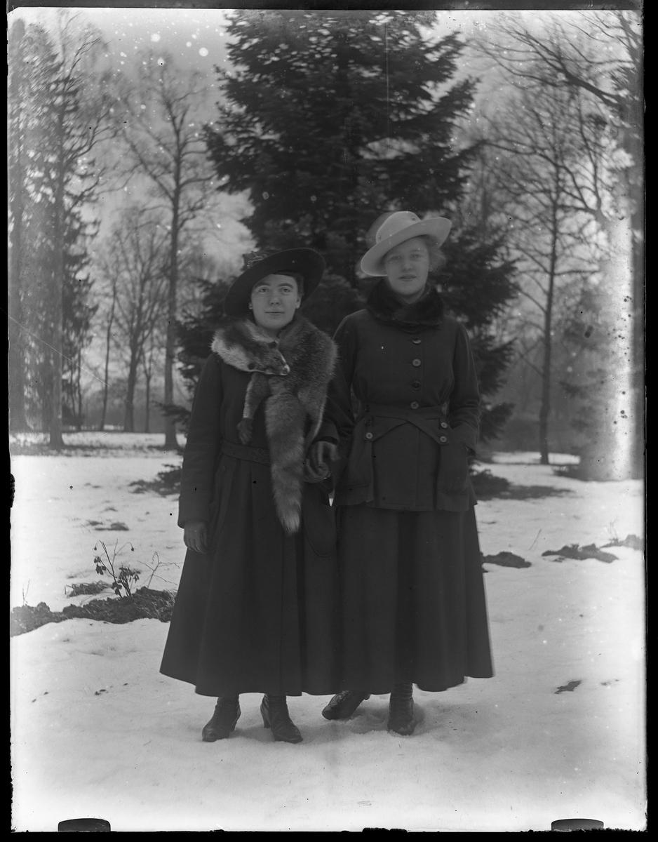 Signe och Eva fotograferade hand i hand ute i snön.