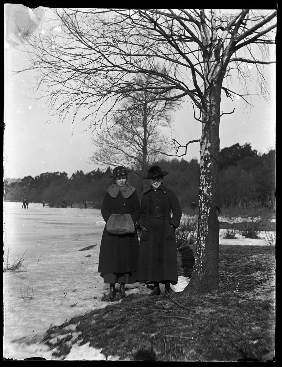 Tulli Thorsell med vän, båda klädda i svart, står på stranden. Längre bort åker några skridskor på sjön.