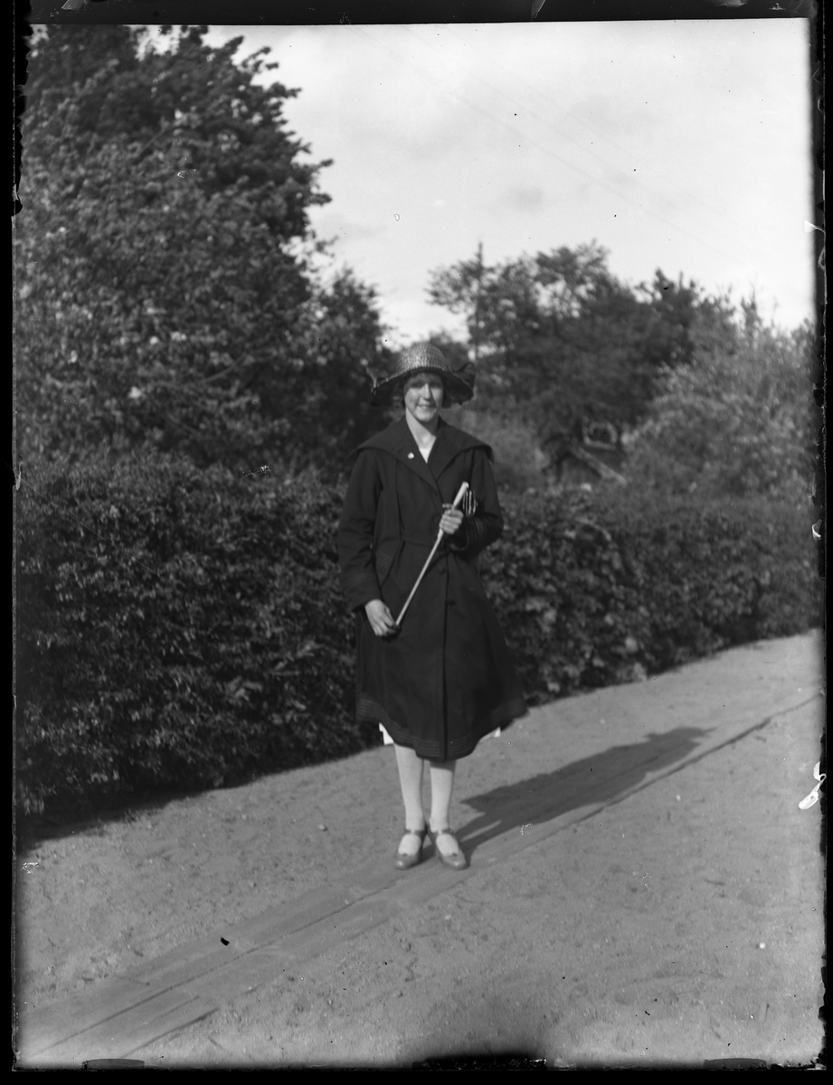 """Porträtt av Lydia Landin klädd i svart kappa och svart hatt stående på en grusväg framför buskar. I fotografens katalog såtr """"Lydia Landin (Skara)""""."""
