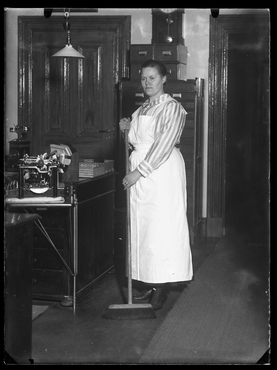 Fru Johansson porträtterad med sopkvast på ett av Alingsås Bomullsväveris kontor.