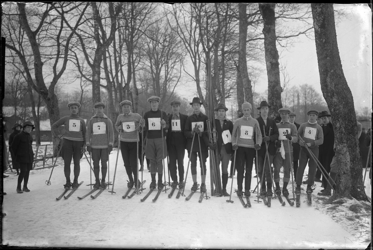 Deltagare i Alingsåsmästerskapen på skidor på sträckan 1 mil. 11 män är uppställda på rad, med nummerlappar på bröstet och skidor på fötterna. Åskådare syns på båda sidor om dem.