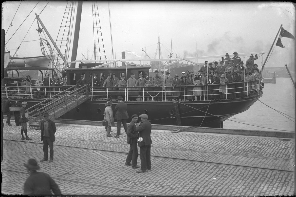 Ett passagerarfartyg ligger inne i hamnen och görs redo för avfärd. Ett antal passagerare står på däck och på kajen står också människor. I fotografens egna anteckningar står: Danmarksresan, Fiona i Göteborgs hamn.