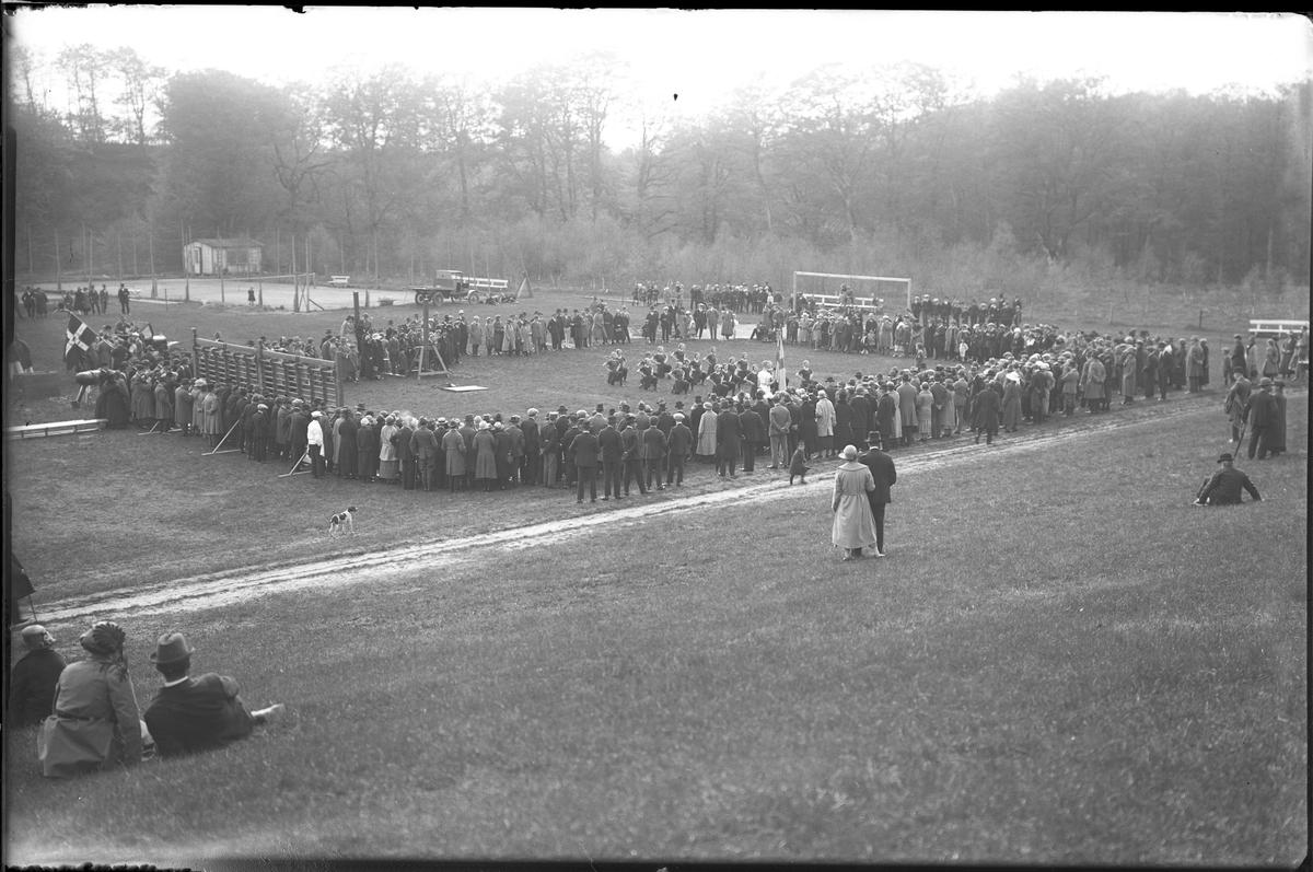 På en gräsmatta har en gymnastiktrupp uppvisning inför en cirkel av åskådare. I fotografens egna anteckningar står: Danmarksresan, Uppvisning i Saeby.