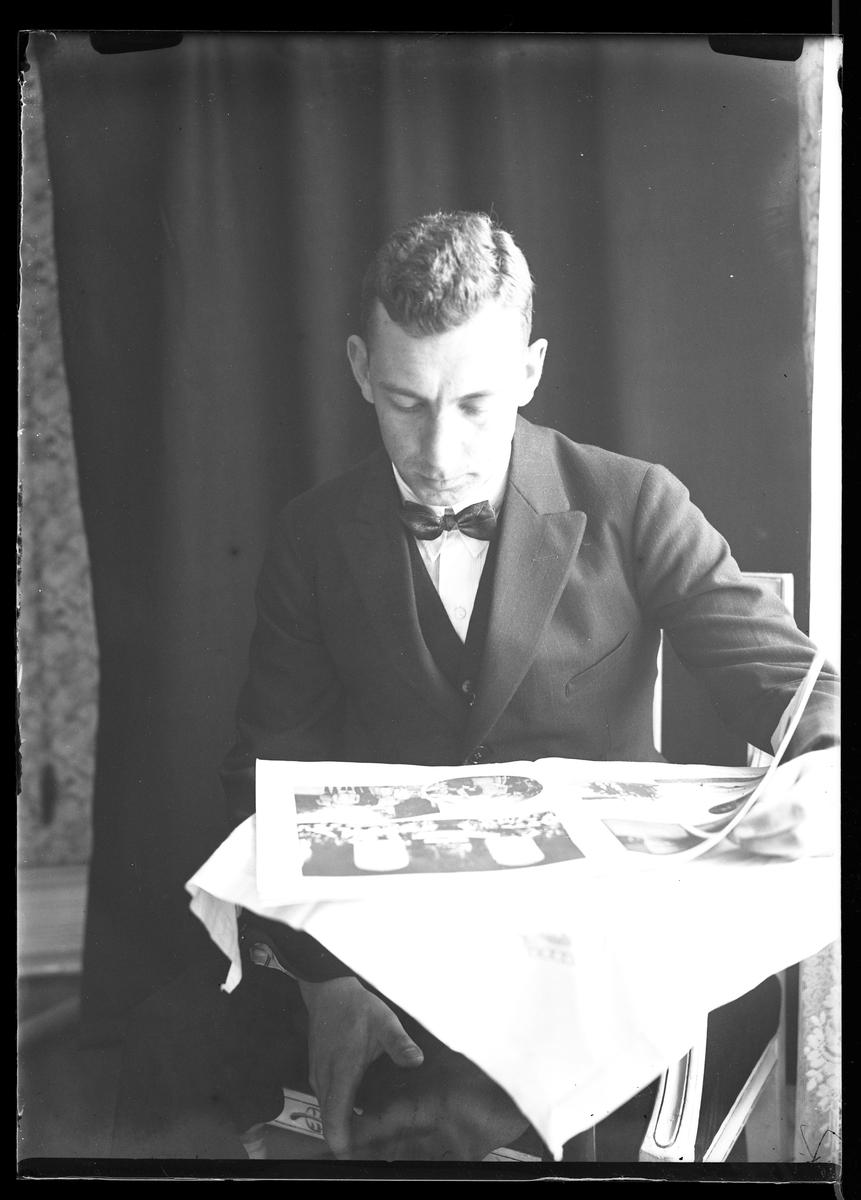 Porträtt av fotografen själv när han sitter vid ett bord och läser tidningen. Bakom honom hänger ett svart draperi.