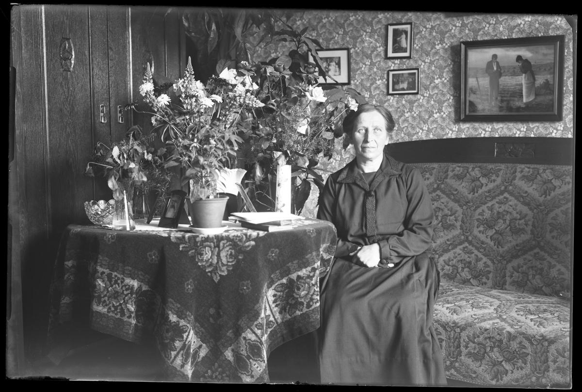 Augusta Ax fotograferad sittandes i en soffa i ett finrum i samband med sin 60årsdag. Bredvid henne på ett bord står blommor och kort.