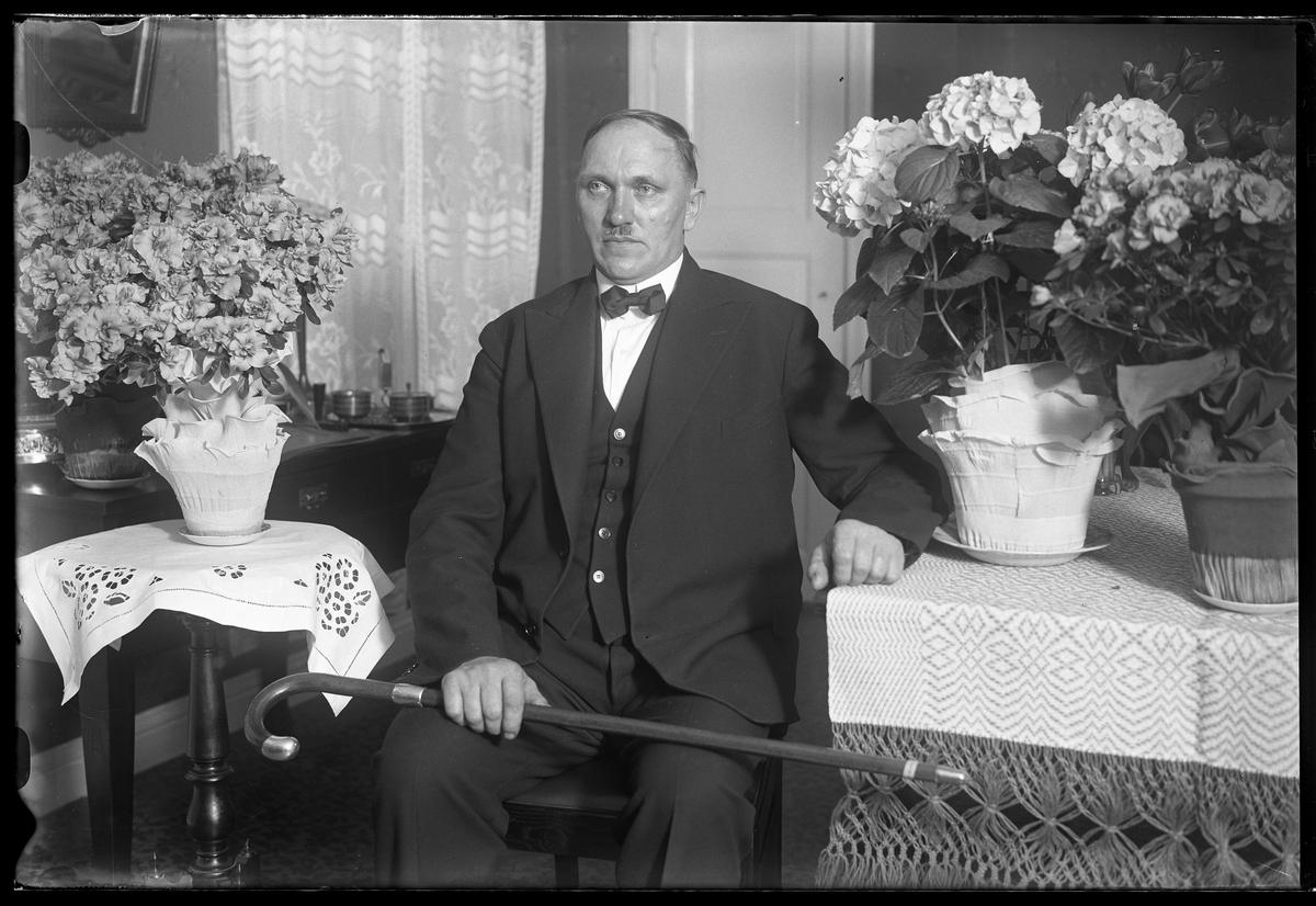 Herr Andersson sitter i ett finrum omgiven av blommor och med en promenadkäpp i handen. Bilden är tagen i samband med hans 50årsdag.