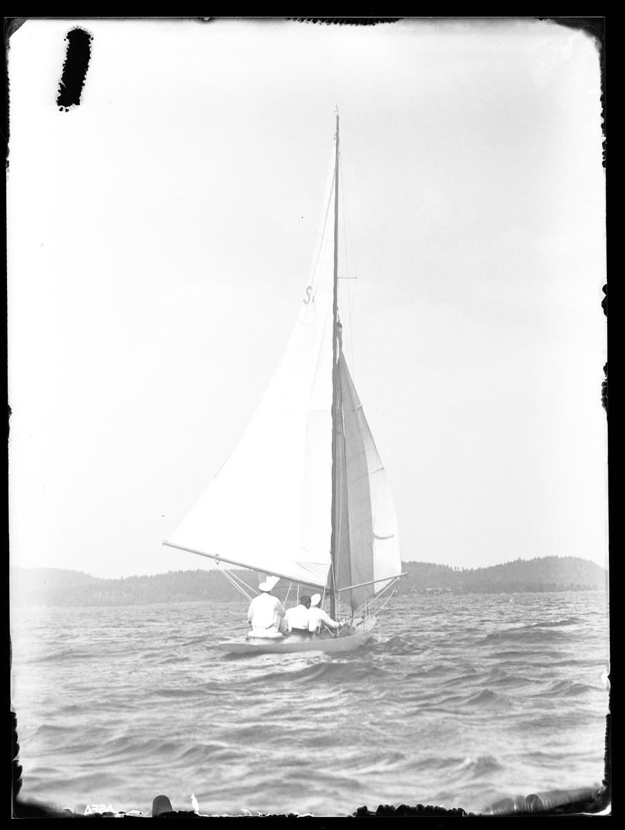 Alingsås Segelssällskaps utlåtningsbåt fotograferad ute till sjöss med tre personer ombord.