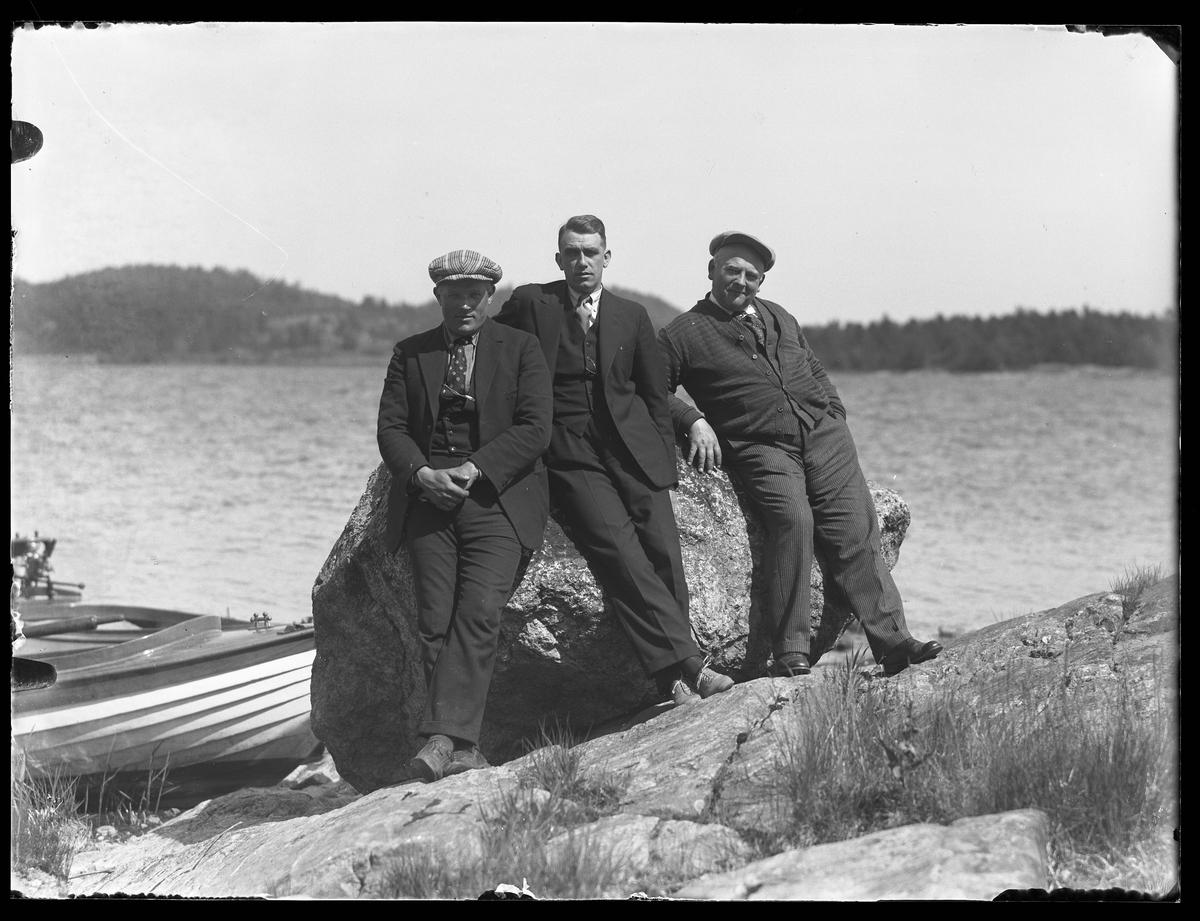 """Tre mån står lutade mot en sten på en klippa vid en sjö. Bakom dem ligger en båt förtöjd. I fotografens egna anteckningar står """"Olle, Andersson, Sandin, Kvarnholmen"""""""