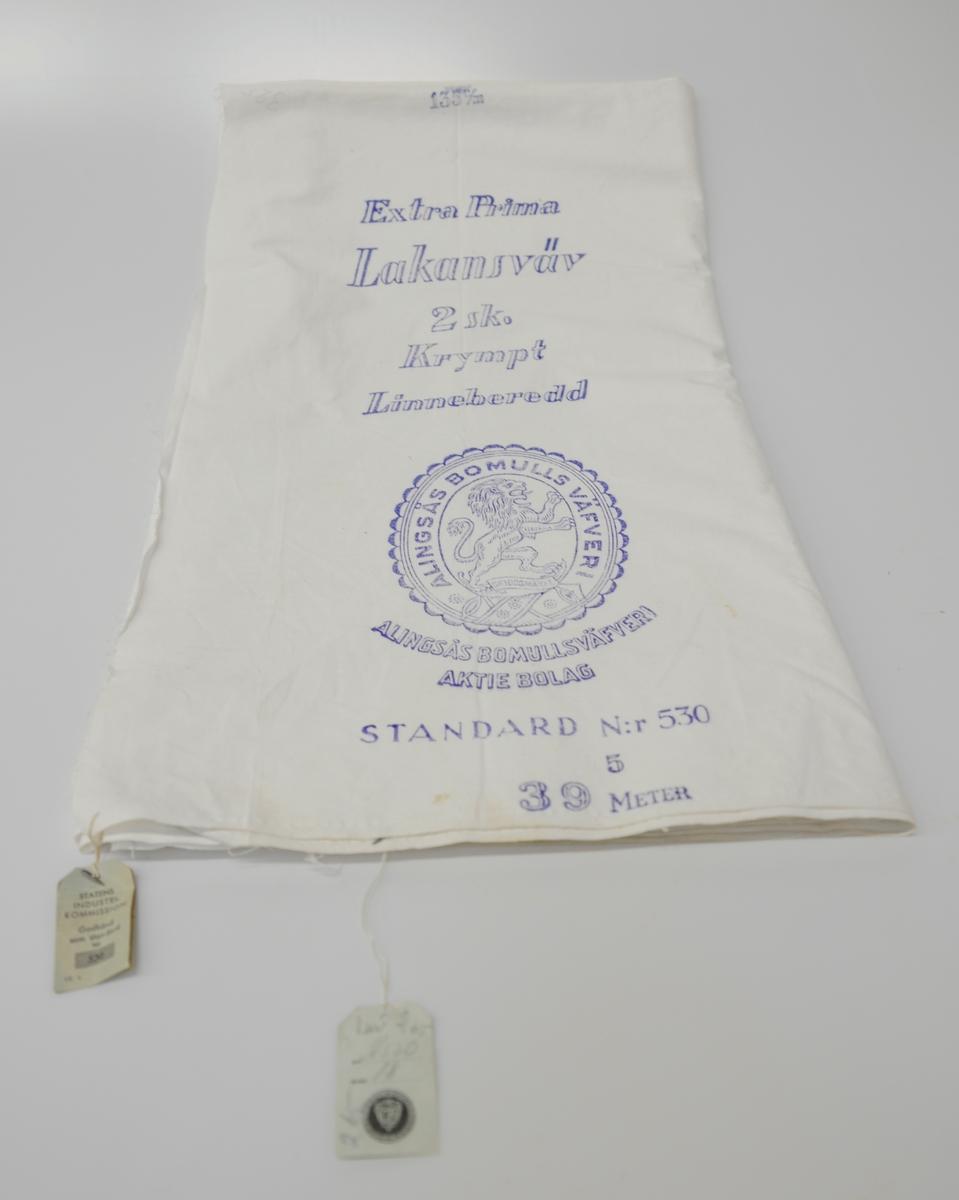 """Vit lakansväv med blå tryckt text: """"135 c/m Extra Prima Lakansväv 2sk. Krympt Linneberedd"""" Företagsstämpel från """"Alingsås Bomulls Väfveri"""" med ett stegrande lejon i profil. Under emblemet står """"Alingsås Bomullsväfveri Aktiebolag Standard N:r 530; 5; 39 meter"""""""