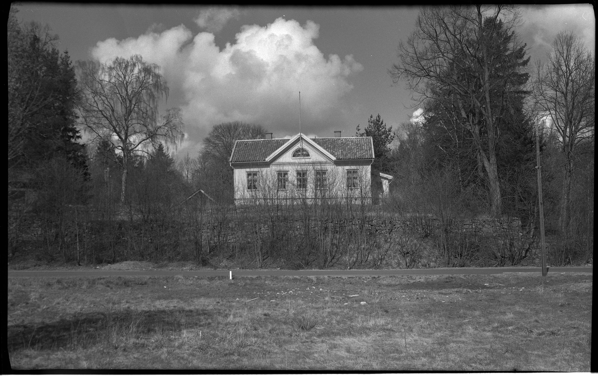 Villa Charlottenberg (Hedvigsberg) på Göteborgsvägen. Framför huset, som ligger på en liten höjd, går en landsväg, Göteborgsvägen. Stora träd omringar huset och på himlen bakom syns stora moln.