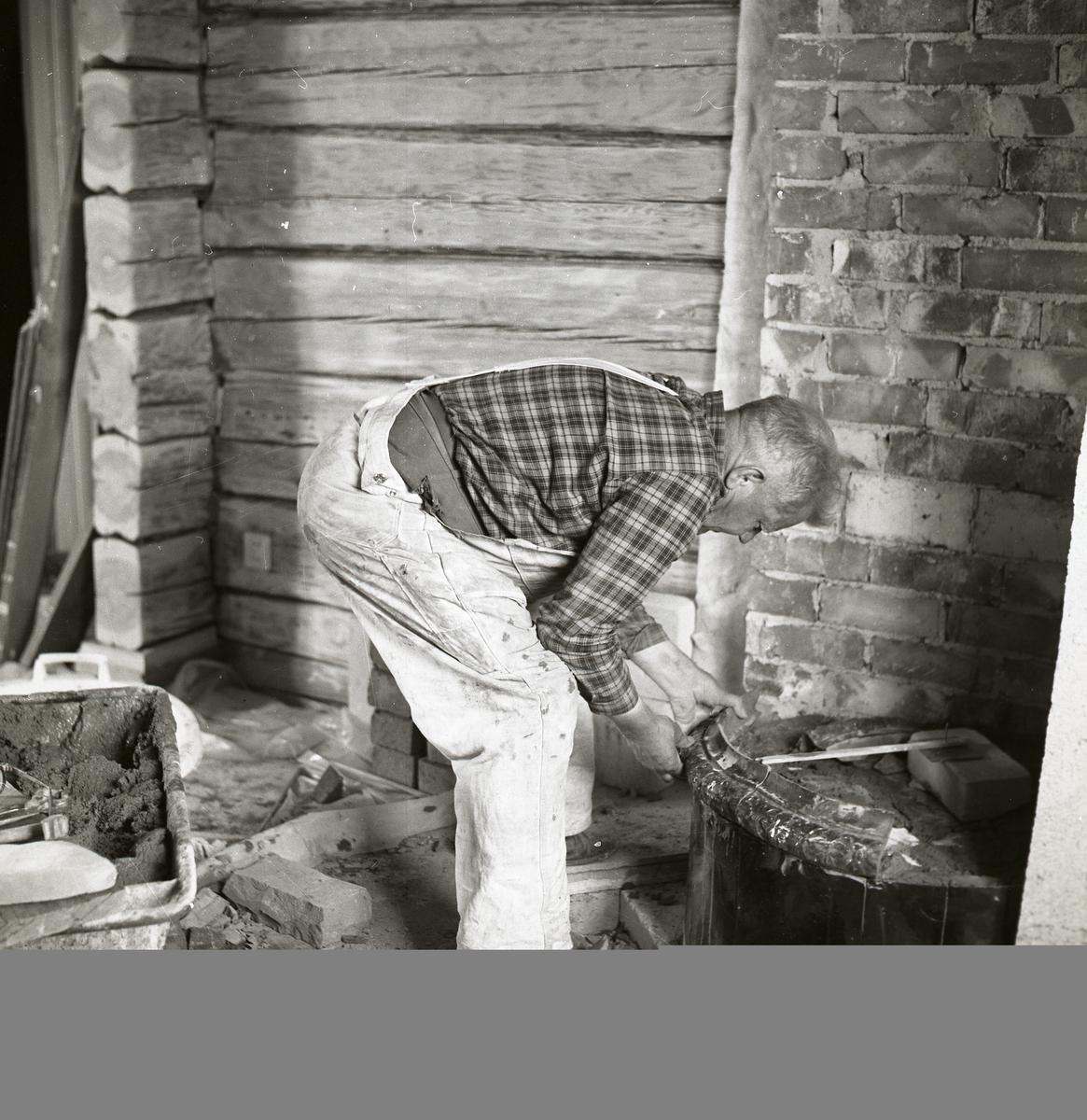 En man bygger ihop en kakelugn, 1968.