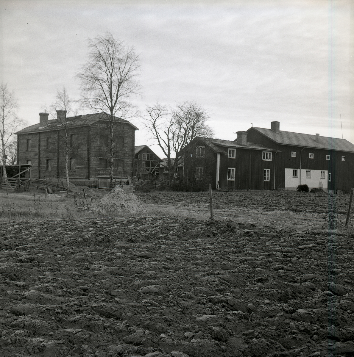 En gård med många byggnader bakom plöjd åkermark den 19 november 1967.