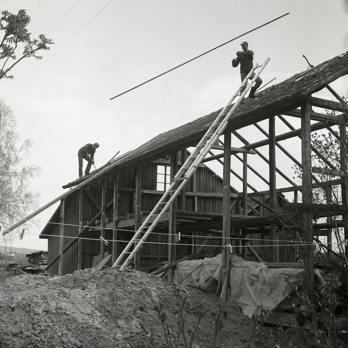 Två män arbetar med rivning av en byggnad.