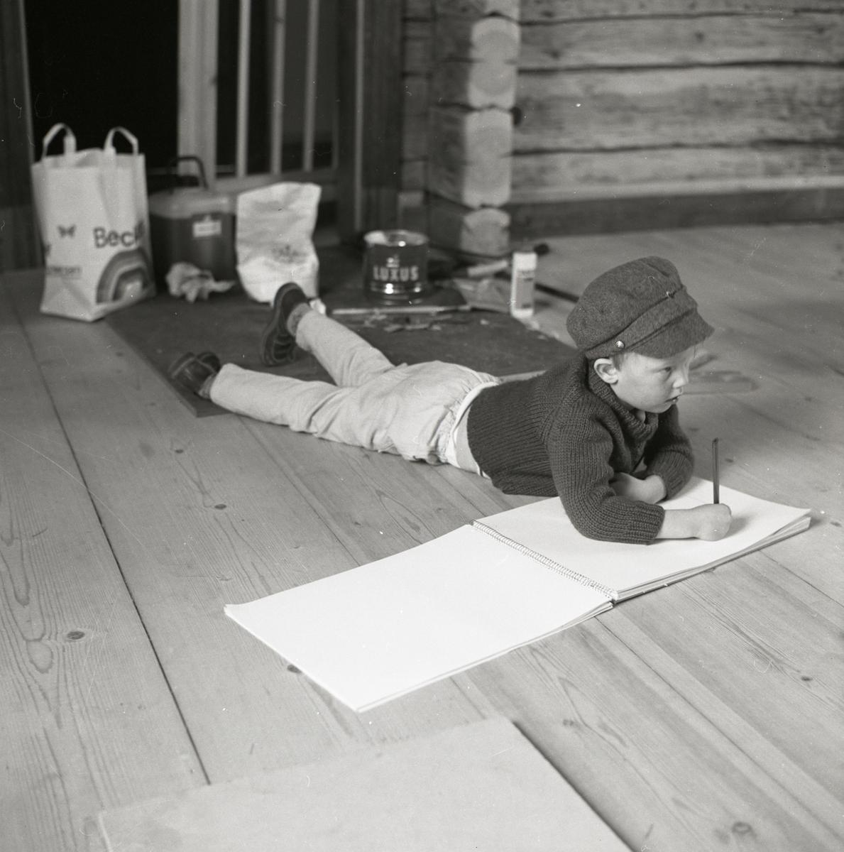 I ett rum på gården Sunnanåker ligger en pojke på golvet och ritar, 1968-1969.