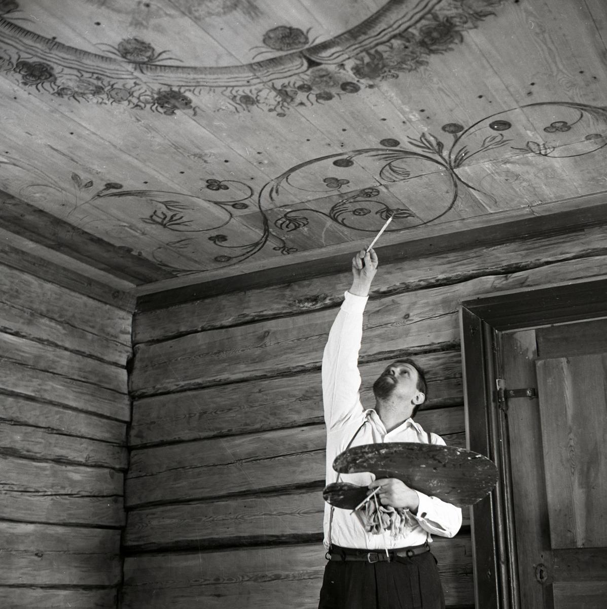 En man målar en takdekorationen vid byggnaden av gården Sunnanåker, 1968-1969.