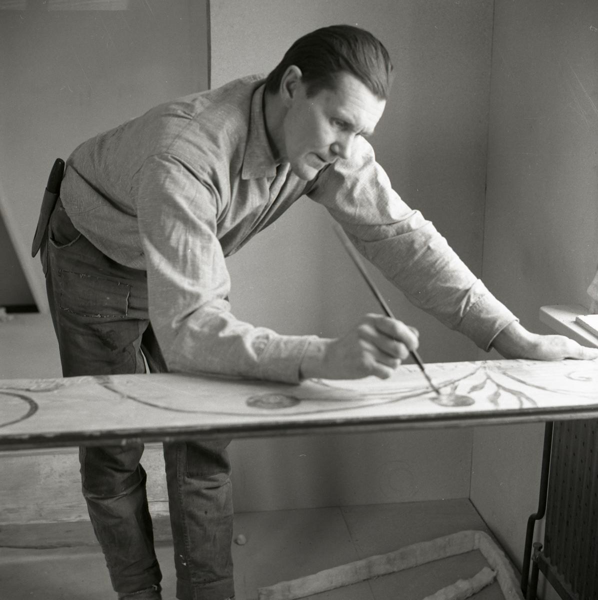 Hilding målar på en takbräda med en pensel, 1968-1969.