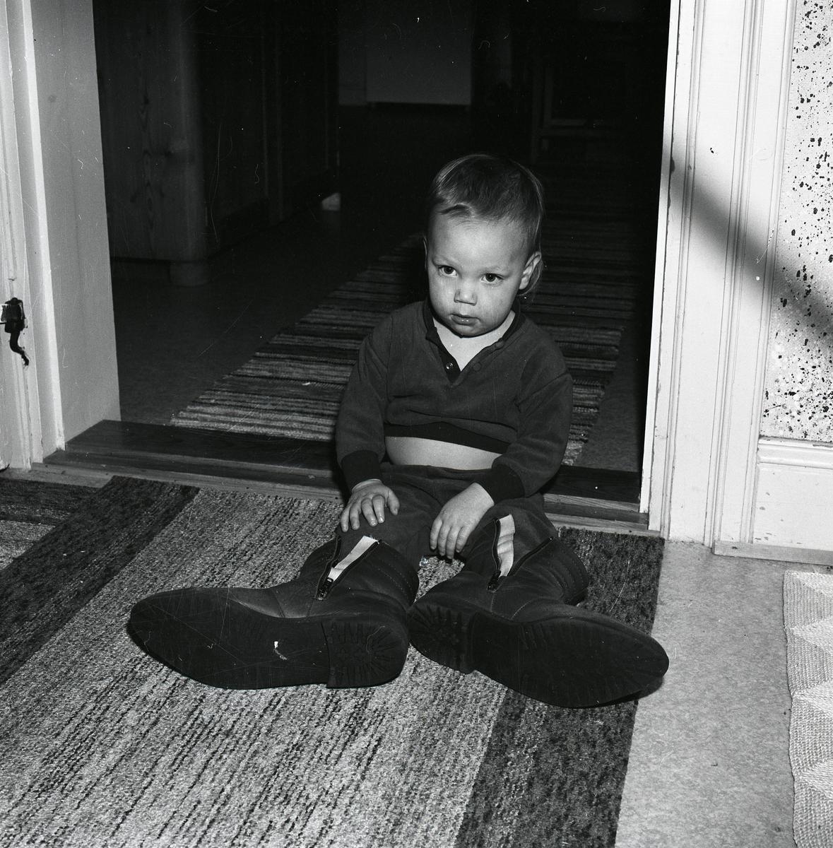 Ett litet barn sitter på en matta på golvet och provar mycket stora skor.