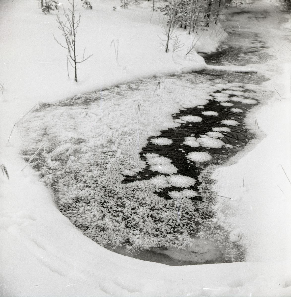 Rimfrost bildar ismönster på ett vattendrag.