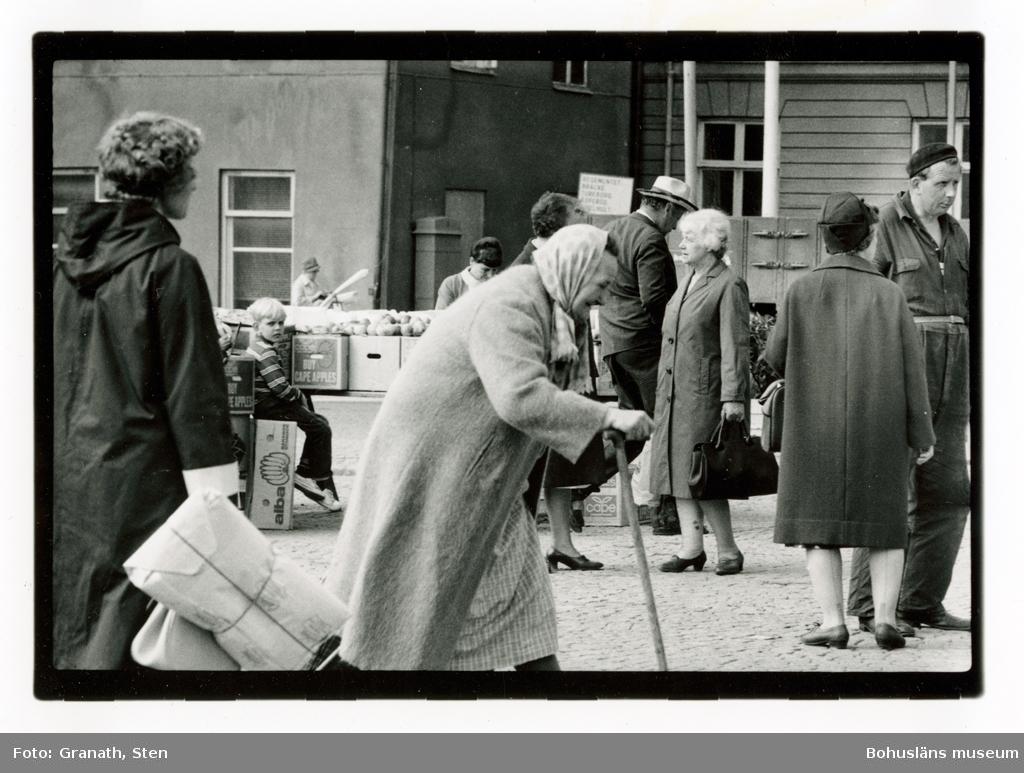 Torgliv i Uddevalla. I bildens centrum går en äldre kvinna med sjal om huvudet och käpp i höger hand åt höger. Till vänster står en kvinna med ryggen mot betraktaren som bär paket och en väska. Mellan dessa, längre bort från betraktaren, syns ett fruktstånd och vid detta sitter en pojke på en banankartong. Till höger i bild rör sig flera personer över torget och några står och samtalar. I bakgrunden syns rådhusets fasad.