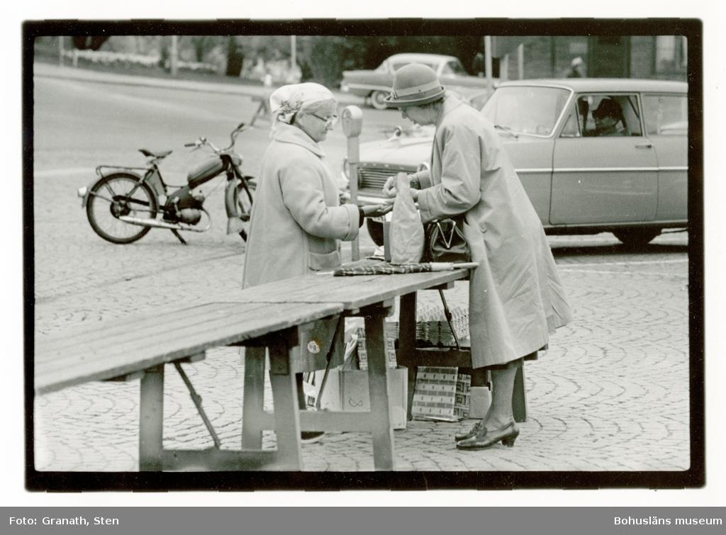 Torgförsäljning. Två kvinnor står på var sin sida om ett bord uppställt på ett torg. Kvinnan till höger har hatt och kappa och ger kvinnan till vänster pengar. Hon har kappa och en sjal knuten runt håret. Mellan dem på bordet står en papperspåse. Under bordet står äggkartonger och lådor. Bakom dem står en bil och en moped parkerade.