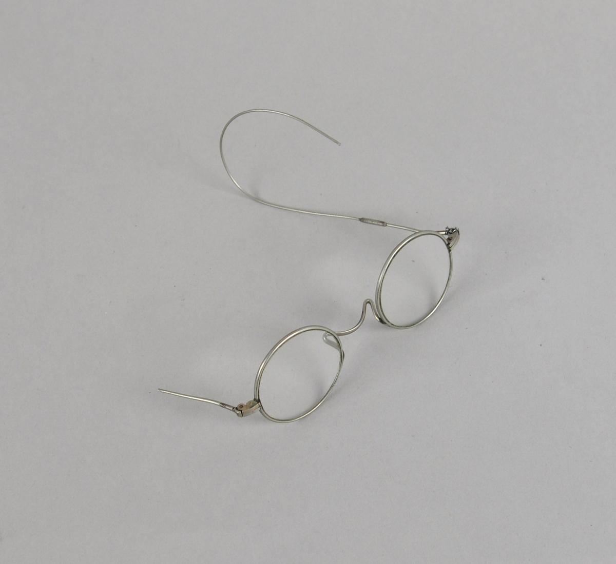 Runde briller med metallinnfatning. Den ene brillestangen er knekt, den andre er  er buet rundt øret.