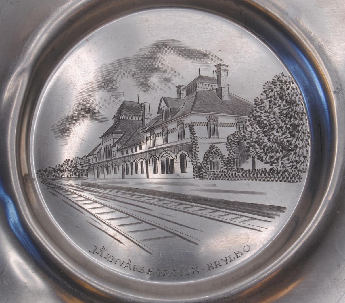 Fat med graverat motiv av stationshus och en del av spåret, sett från ett anländande eller lämnande perspektiv.