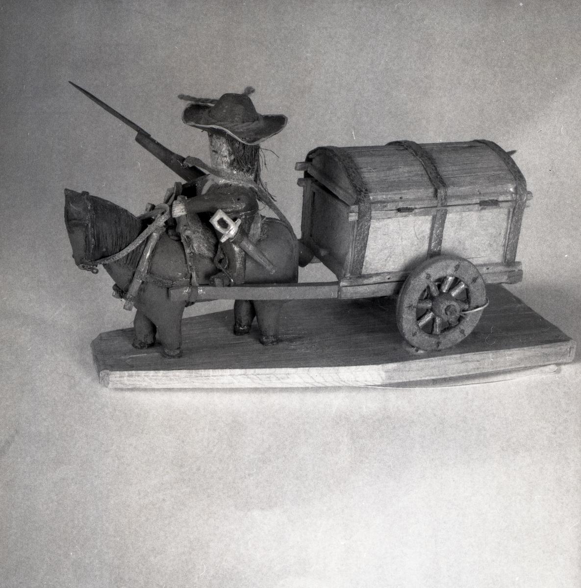 En trämodell av häst med vagn som framförs av en man med gevär och hatt.