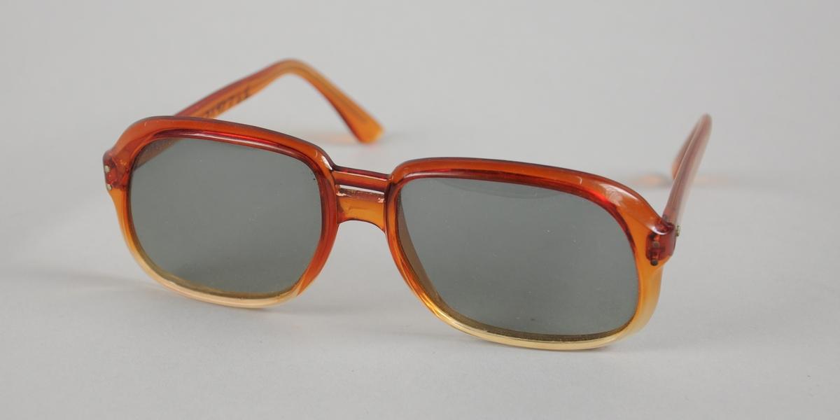 Solbrille med firkantede mørke glass som med avrundede kanter. Innfatning og stenger av plast.