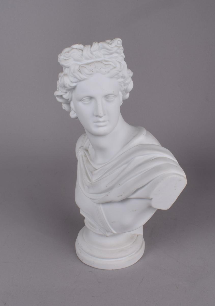 Klassisk mannsfigur med håret i sløyfe og draperier rundt skuldrene. Den romerske/greske guden Apollo