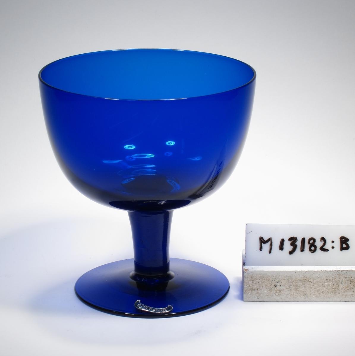 """Dricksglas på ben och fot. Mörkblått, tämligen klart glas. Ovan angivna mått avser övre diameter. Fotdiameter: 76 mm. Bananformad, mörkblå etikett med text. Se """"Signering, märkning"""" ovan. Inskrivet i huvudkatalogen 1943.  Se M 15185 och M 15186, samma modell. Funktion: Dricksglas, eventuellt för alkoholhaltig dryck"""